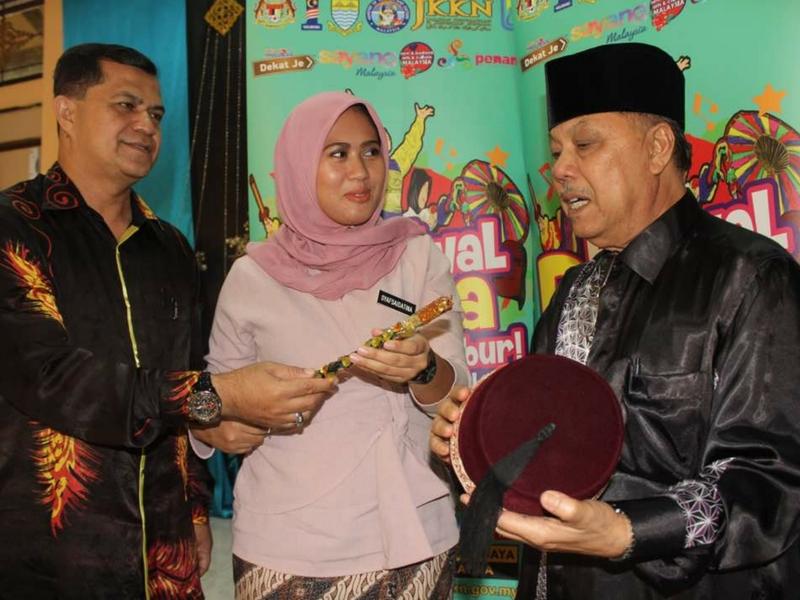 Norsyahrul Syafsaidatina Ismail (tengah) melihat tarbus dan tongkat yang digunakan dalam persembahan boria yang ditunjukkan Zahir Ahmad (kiri) dan Datuk Anuar Ahmad ketika sidang media Festival Boria 2017 di Pulau Pinang baru-baru ini.