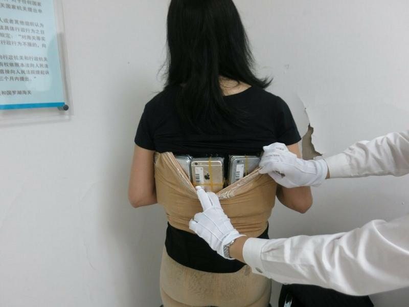Wanita terbabit menunjukkan cara iPhone 7 Plus dilekatkan di belakang badannya.
