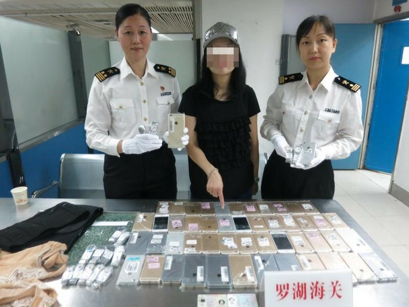 Siapa sangka wanita berbaju hitam ini berani menyeludup 102 iPhone 7 Plus bersama 15 jam tangan Tissot.