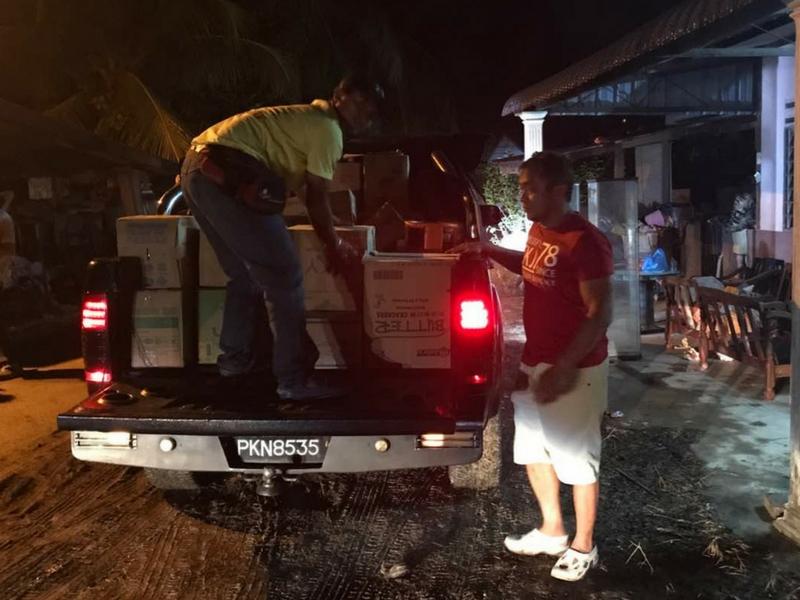 Dua wakil PSBC sedang menurunkan barangan bantuan banjir.
