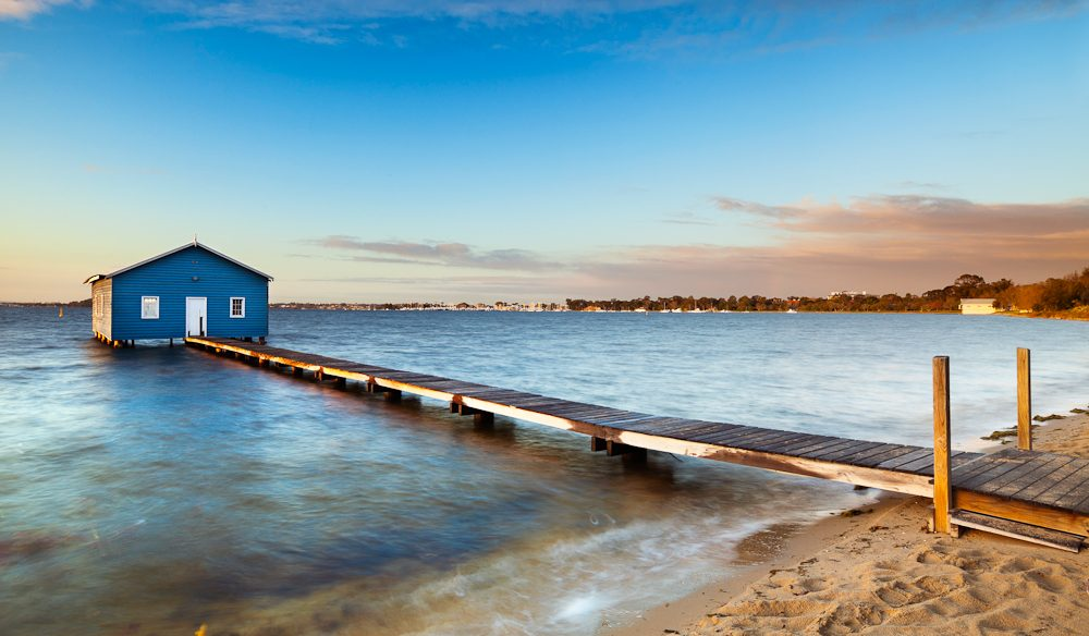 The iconic boat shed sits atop the calm waters of Swan River.