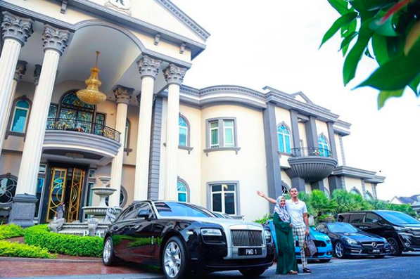 Aliff standing in front of his house and cars.