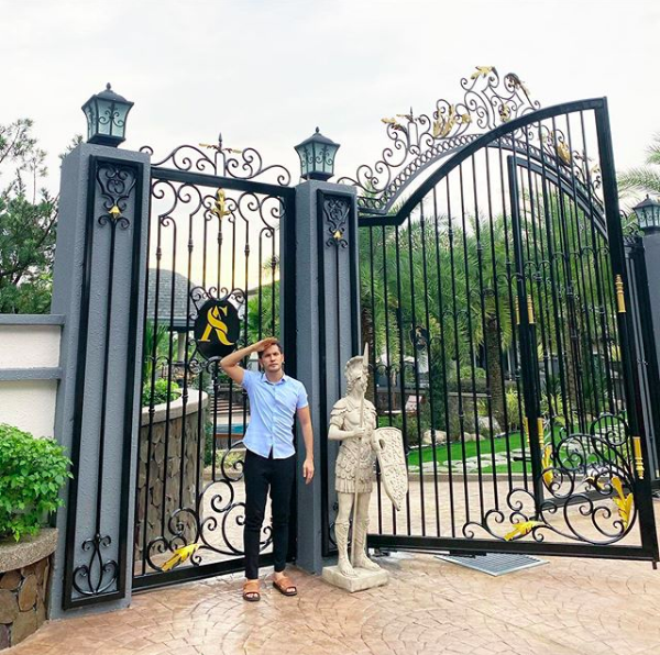 Aliff standing in front of his house gates.