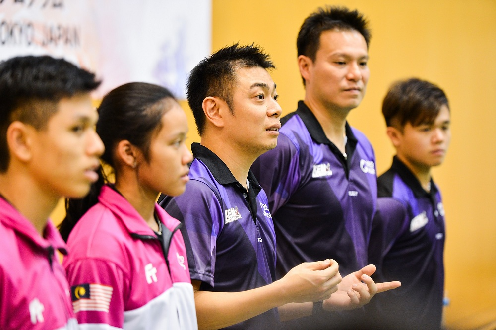 Jacky and Myisha standing alongside AKB head coaches Lee Wan Wah and Chan Chong Ming.