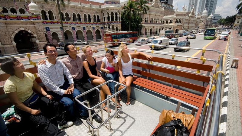 The KL Hop-On Hop-Off bus is popular among international visitors. They're not even afraid of the hot sun!