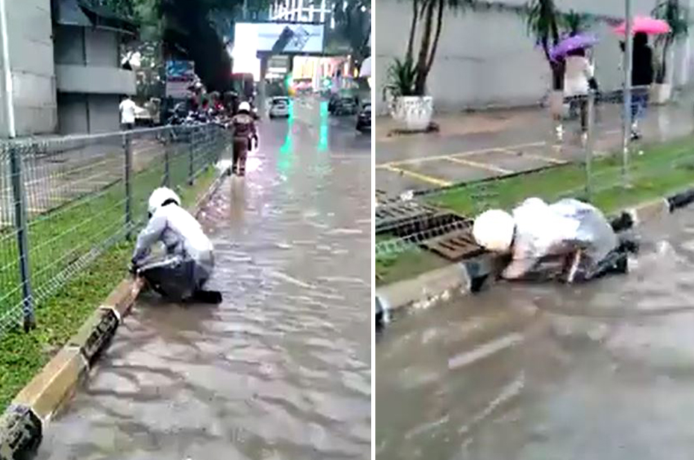 'Abang Polis' Wins Praises For Unclogging Drain With Bare Hands To Ease Traffic Flow