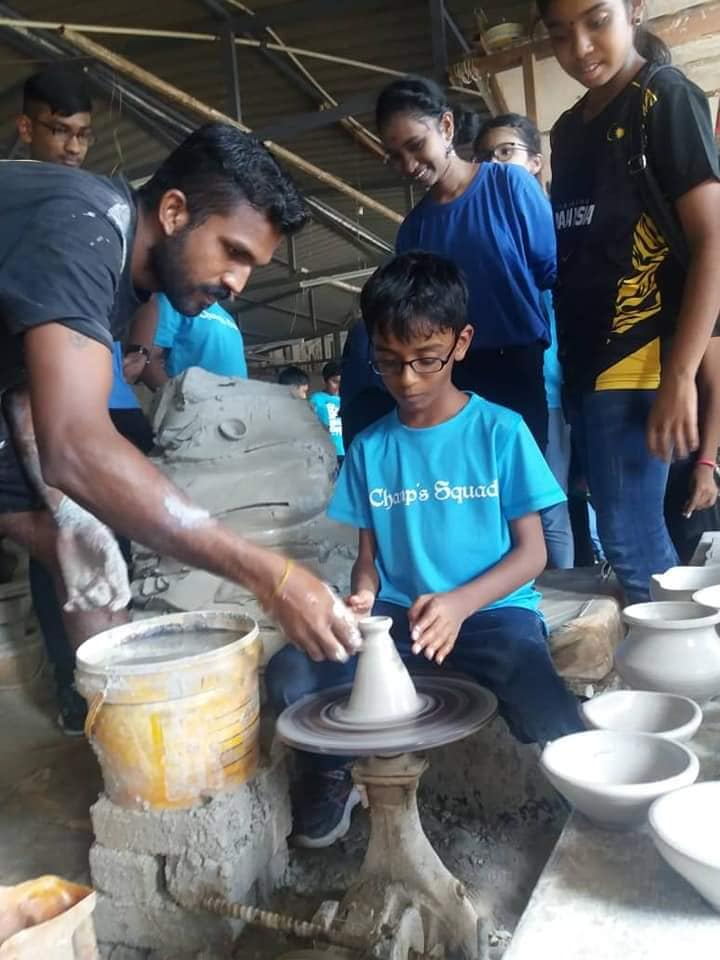 Mahavisnoo (left) teaches kids how to make a clay pot.