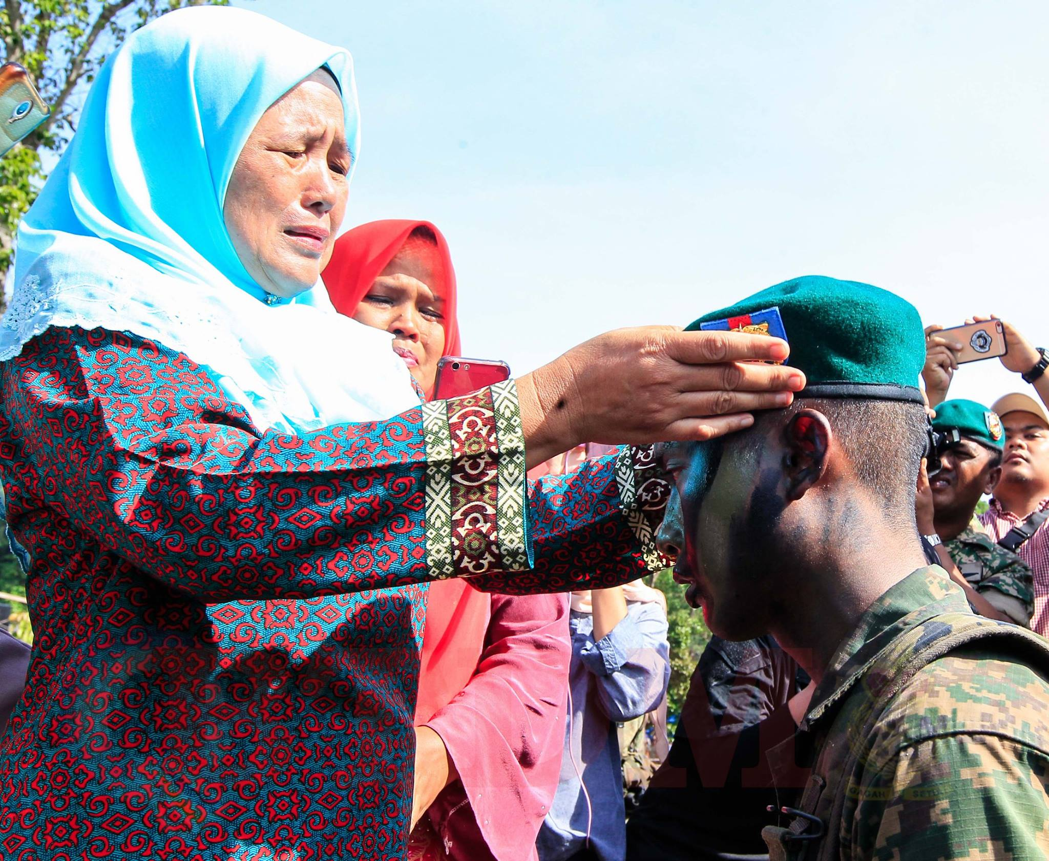 2nd LT Nizam's mother does the honour of putting the green beret on her son's head.